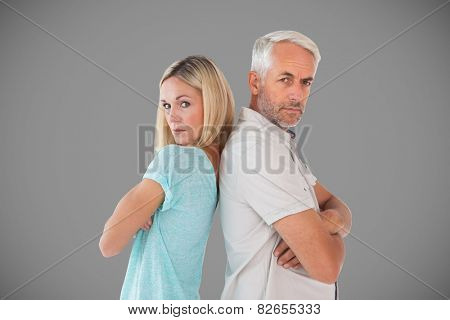 Unhappy couple not speaking to each other against grey