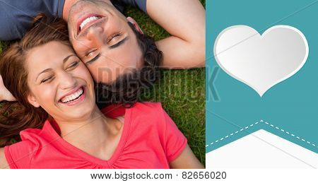 Two friends smiling while lying head to shoulder with an arm behind their head against heart label
