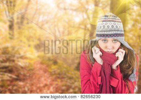 Cold redhead wearing coat and hat against tranquil autumn scene in forest