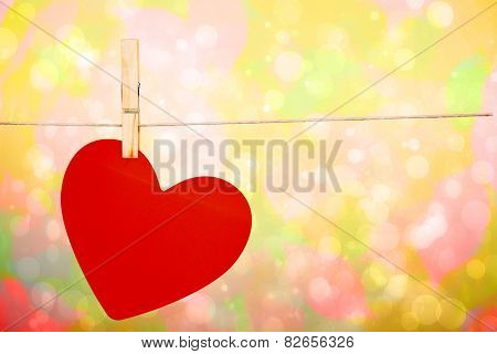 Heart hanging on line against girly pink and yellow pattern