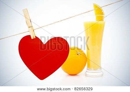 Heart hanging on line against orange placed next to a glass of orange juice