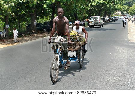 African Man Rides His  Tricycle With Body.