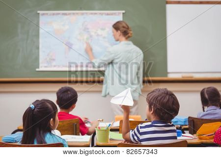 Naughty pupil about to throw paper airplane in class at the elementary school