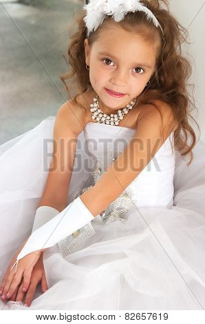 The Elegant Girl In A White Ball Dress Sits On A Window Sill