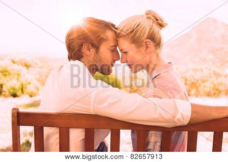 Cute couple sitting on bench together smiling at each other on a sunny day