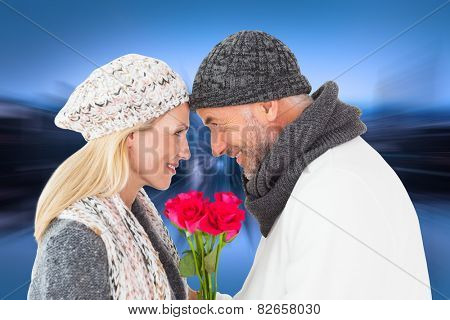Smiling couple in winter fashion posing with roses against mirror image of city skyline
