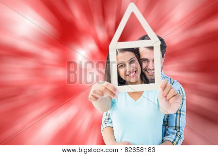 Happy young couple with house shape against digitally generated twinkling light design