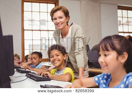 Cute pupil in computer class with teacher smiling at camera at the elementary school