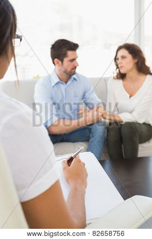 Couple talking with their psychologist in the office