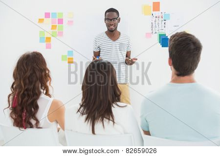 Smiling businessman presenting at his colleagues in the office