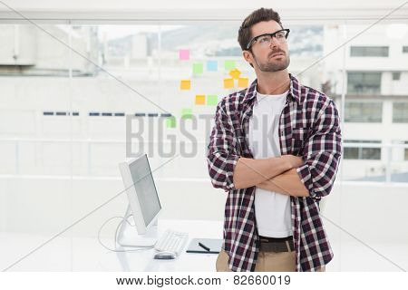 Thoughtful businessman with arms crossed standing in the office