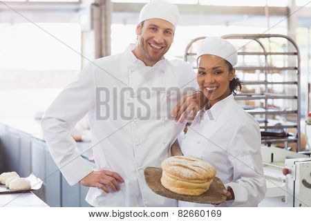 Team of bakers smiling at camera with loaf in the kitchen of the bakery