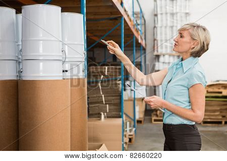 Warehouse manager checking her list on clipboard in a large warehouse