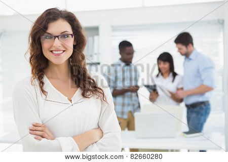 Smiling businesswoman with arms crossed in front of her colleagues