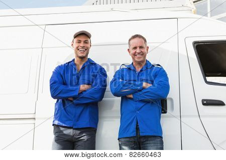 Smiling handymen looking at camera in front of their van