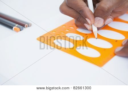 Hand of businessman using stencil and pencil in the office