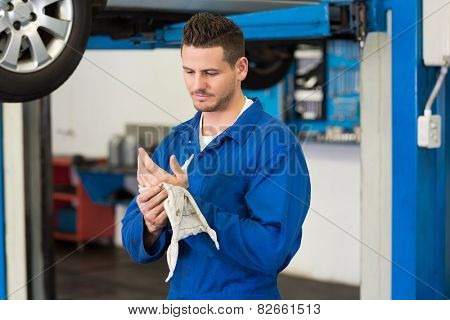 Mechanic wiping hands with rag at the repair garage