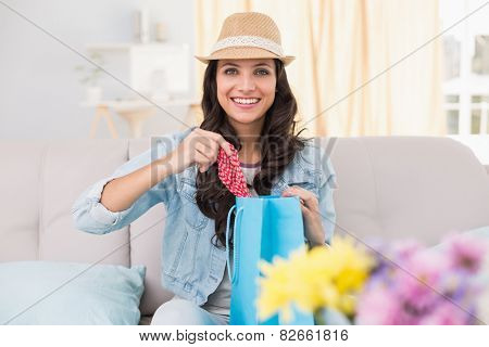 Pretty brunette opening shopping bag at home in the living room