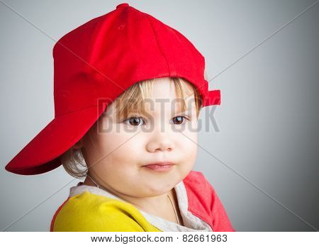 Portrait Of Funny Little Child In A Red Baseball Cap
