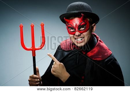 Funny devil against dark background