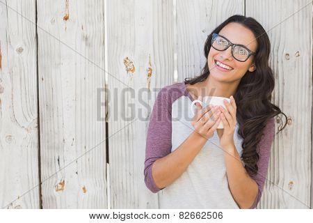 Pretty brunette holding a mug against bleached wooden fence