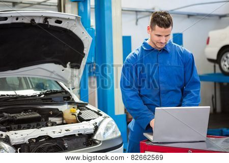 Concentrated mechanic using his laptop at the repair garage