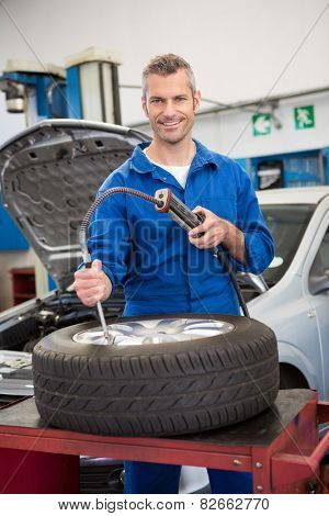 Smiling mechanic inflating the tire at the repair garage