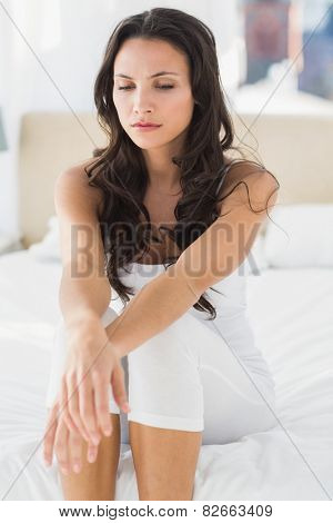 Worried brunette sitting on bed at home in bedroom