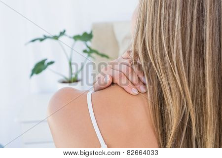 Rear view of woman getting neck pain at home