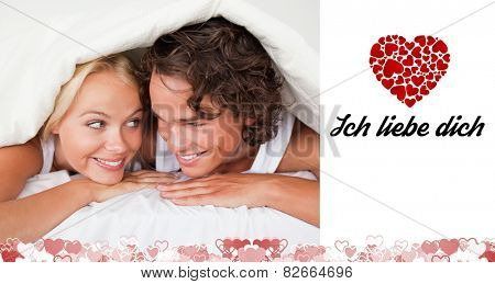 Couple under a duvet with a knowing smile against ich liebe dich
