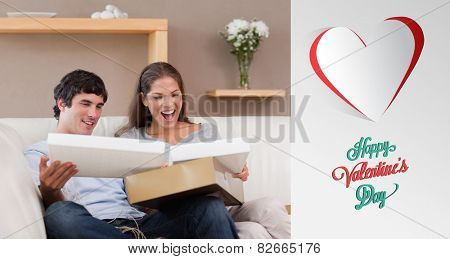 Couple on the couch opening parcel against cute valentines message