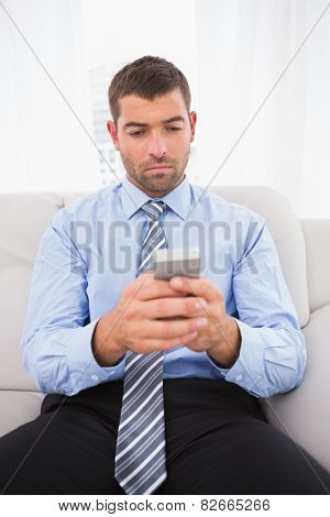 Concentrate man using his phone at home sitting in a sofa