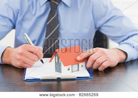 Businessman taking notes and holding miniature house in his office