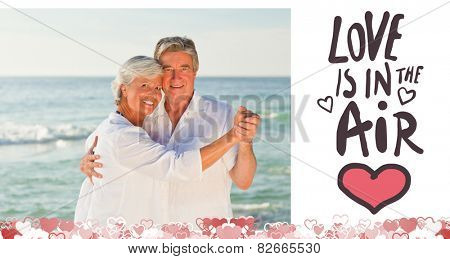 Mature couple dancing on the beach against love is in the air