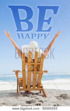 Woman sitting in deck chair at the beach with arms up against be happy