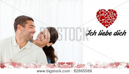 Lovely couple laughing together in the living room against ich liebe dich