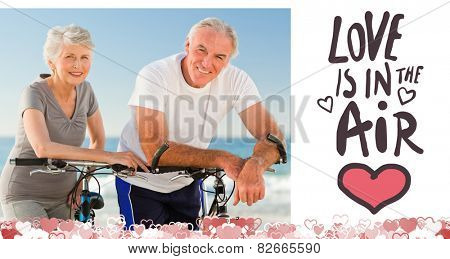 Retired couple with their bikes on the beach against love is in the air