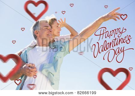 Happy senior man giving his partner a piggy back against happy valentines day