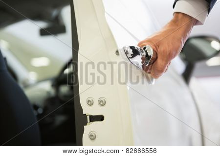 Man holding a car door handles at new car showroom