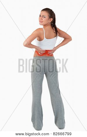Back view of woman with backache against a white background