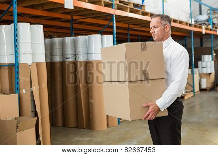 Warehouse manager carrying cardboard boxes in a large warehouse