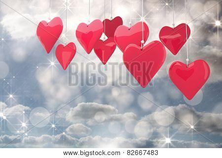 Love hearts against shimmering light design on grey