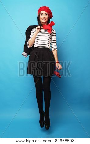 Beautiful girl in a red beret. French style. Over blue background.