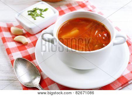 Ukrainian beetroot soup - borscht, on napkin, on wooden background