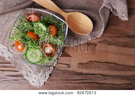 Cress salad with sliced cucumber and cherry tomatoes in glass bowl on rustic wooden table background