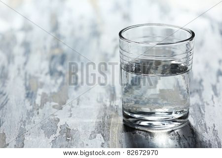Glass of clean mineral water on old color wooden background