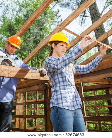 Architect and construction worker working on wooden frame at site