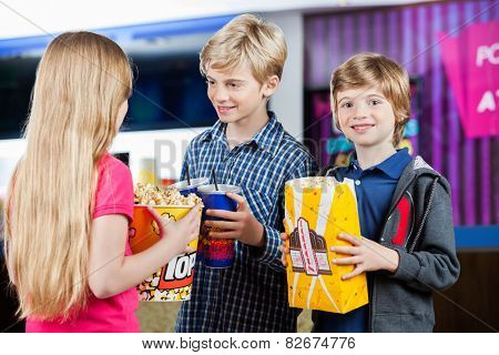 Portrait of happy boy holding popcorn while siblings talking at cinema