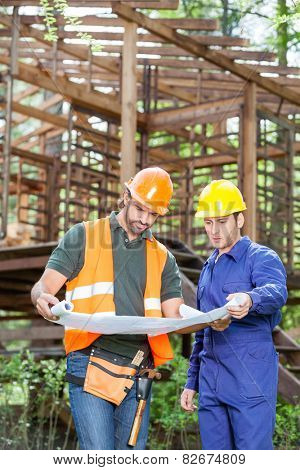 Male architects studying blueprint outside incomplete wooden cabin at construction site