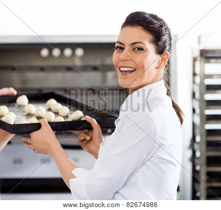 Side view portrait of happy female chef giving baking sheet to male colleague by oven in commercial kitchen